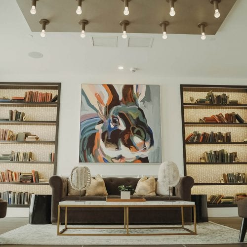 Modern interior living space feature bookshelves and large mural